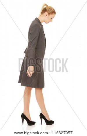 Young business woman looking down.