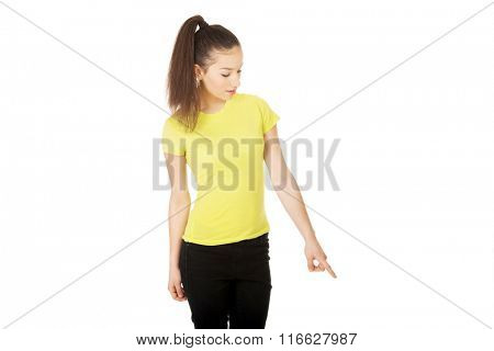 Young woman pointing down.