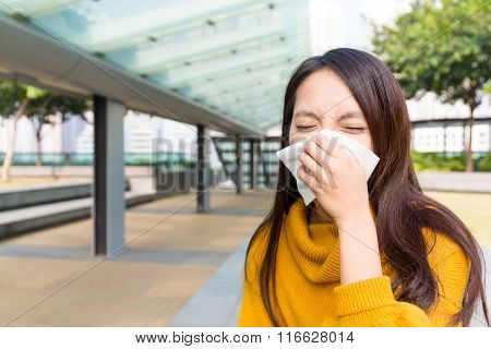 Sick woman with a cold blowing into tissue