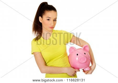 Happy woman holding piggybank.