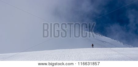 The man at the foot of a mountain peak in the clouds