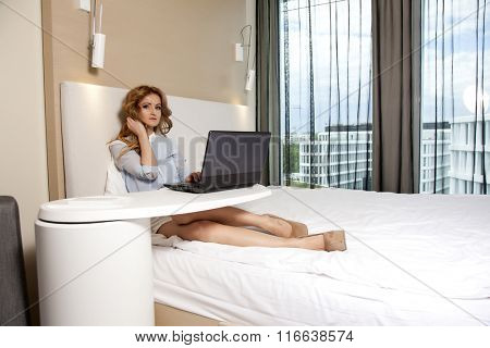 Portrait of a young adult beauty attractive sexy and sensuality happy pretty blonde businesswoman using laptop while lying on bed in bedroom hotel room