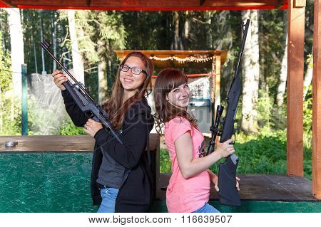 Two Beautiful Female Models Posing With Guns In Shooting Range