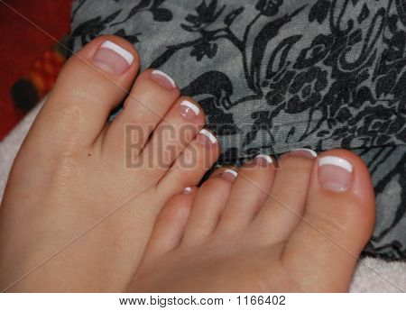 Picture or Photo of Toe nail tips painted white with feet relaxing on a pillow.