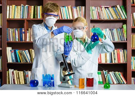 Cute boy and girl doing biochemistry research in chemistry class