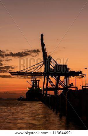 Silhouette Of Container Cargo And Crane Bridge