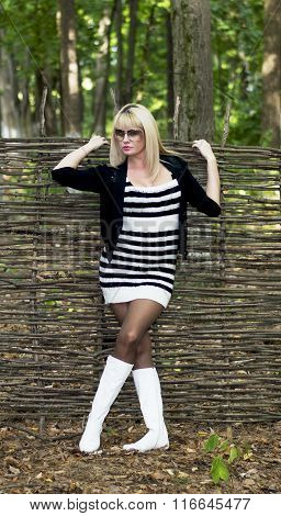 The Blonde With White Boots At A Wattled Fence