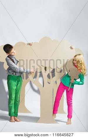 Love concept. Couple of kids. boy and girl hiding behind a cardboard tree