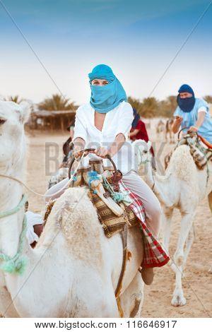 Young Caucasian Woman Tourist Riding On Camel In Sahara Desert
