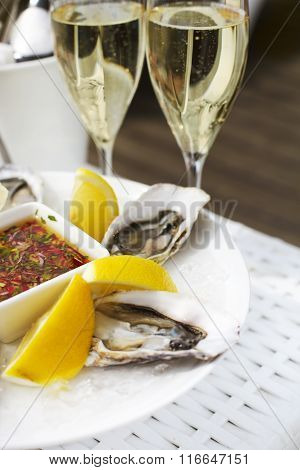 Fresh Oysters Shell With Lemon And Glasses Of Champagne. Top Of View