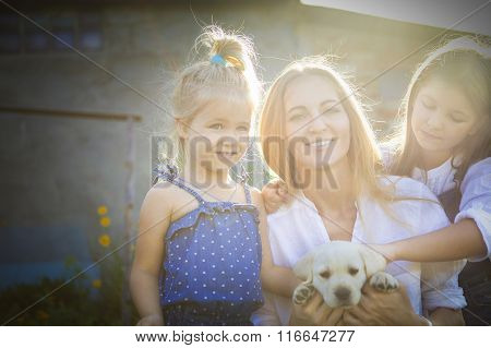 Happy Woman And Her Daughters With Puppy Of Labrador