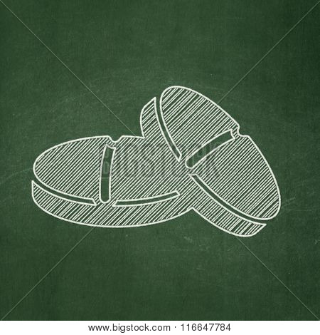 Healthcare concept: Pills on chalkboard background