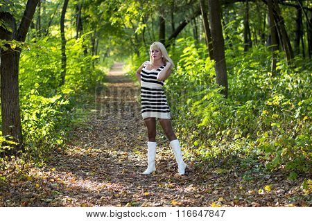The Beautiful Bright Blonde In White Boots On A Forest Footpath In The Fall
