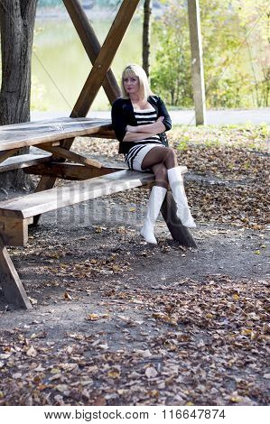 The Beautiful Blonde In White Boots Sits On A Wooden Bench