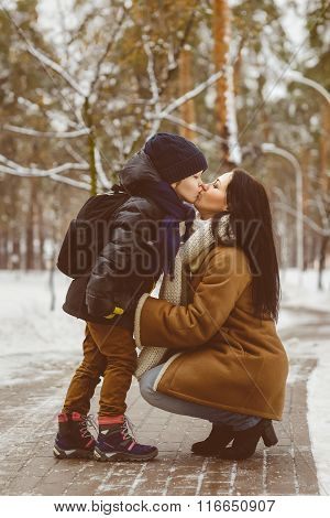 Happy family in winter clothing. Little son kissing his happy smiling mother