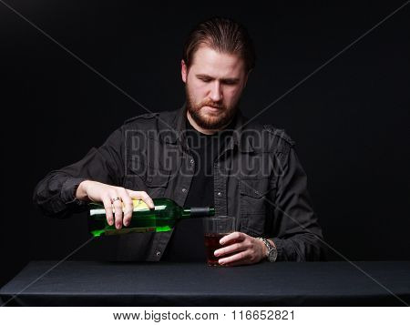 Young Man Is Pouring Out Alcohol From The Bottle  To The Wineglass