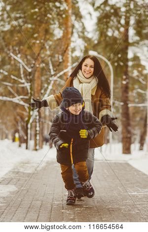 Happy family in winter clothing. Smiling son runs away from his mother outdoor