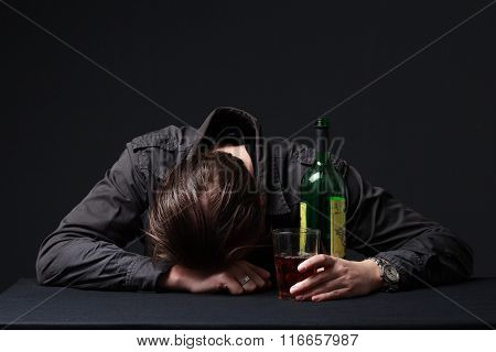 Alcoholic Sleeping On The Table With The Bottle In The Hand