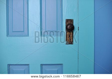 Blue door with old brass doorknob