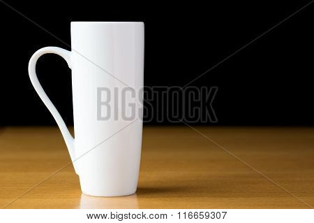 Tall white mug on a wooden table