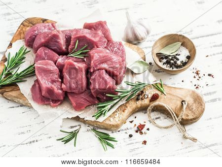 Fresh Raw Chopped Beef, Spices And Herbs On An Olive Board On A Light Wooden Background