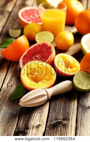 Wooden Juicer And Citrus On A Wooden Table