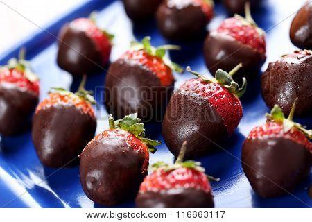 Fresh Strawberries Dipped In Dark Chocolate On Blue Tray