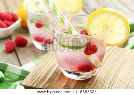 Raspberries And Juice In Glass On Cutting Board On Grey Wooden Background