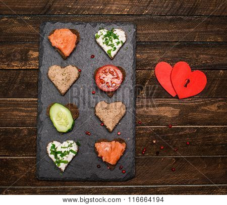 Canapes Heart Shape With Different Toppings On Black Slate Board And Vintage Knife On Rustic Wooden
