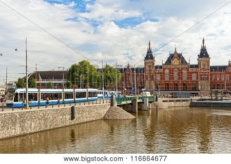 AMSTERDAM, NETHERLANDS - JULY 07, 2015: View of urban tram and Centraal - largest train station of Amsterdam, major national railway hub, designed by Dutch architect Pierre Cuypers and opened in 1889.