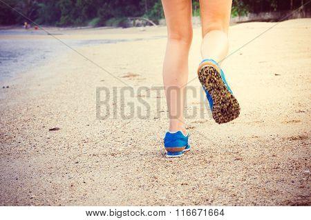 Women's Legs Running Or Walking Along The Beach.