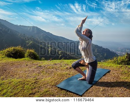 Young woman doing Ashtanga Vinyasa yoga advanced difficult asana Vatayanasana (Horse pose) outdoors in Himalayas mountains. Himachal Pradesh, India