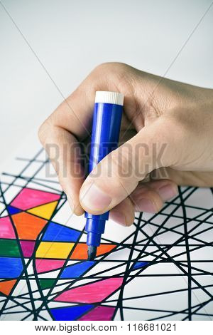 closeup of a young man coloring an abstract drawing, designed by myself, with marker pens of different colors