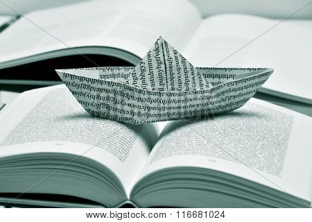 closeup of a paper boat, made with a printed paper with non-sense words, on an open book, in black and white