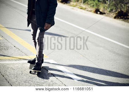 a young caucasian man skateboarding on a non-traffic street, with a vignette added