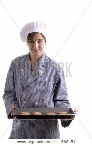 Young Female Cook Presenting A Plate Full Of Chocolate Cookies