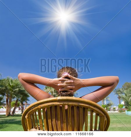 The Girl Sits In An Armchair On A Grass