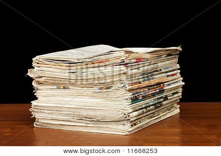 Heap Of Newspapers On A Wooden Table
