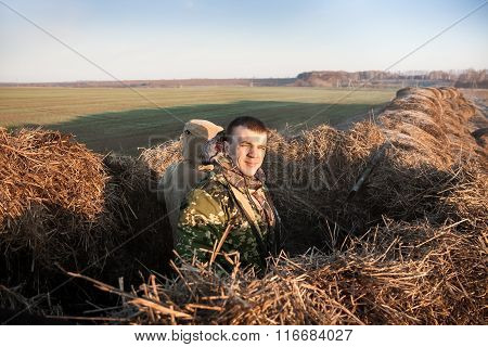 Man hiding in haystack during hunting season at sunrise
