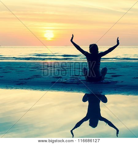 Silhouette of a young woman sitting on the beach during a beautiful sunset, with reflection in the water. Serenity, beauty and health.