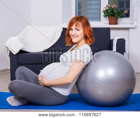 Happy Pregnant Woman Doing Exercises With Fitball In Living Room