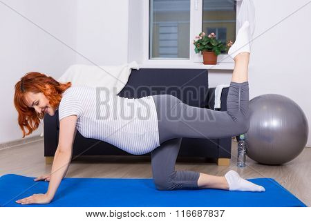 Happy Pregnant Woman Doing Stretching Exercises In Living Room