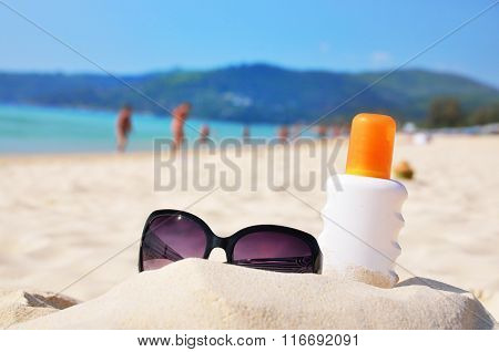 Sunglasses and protection lotion on the beach of Phuket island, Thailand