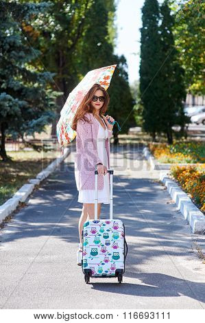 Happy Tourist Woman In Umbrella With Suitcase Walking In Park
