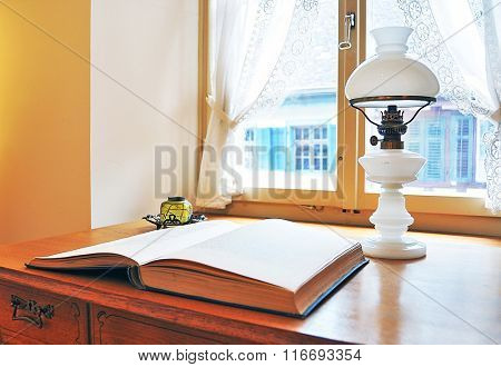 Old petroleum-lamp and a book against window