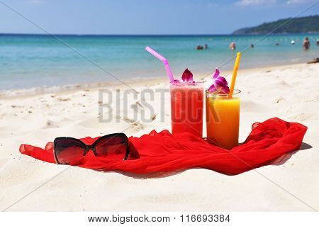 Pair of fruit shakes, red shawl and sunglasses on the beach of Phuket island