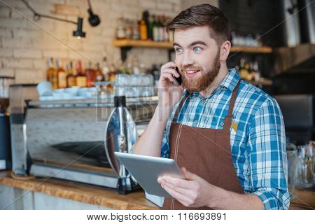 Happy bearded young waiter talking on cell phone and using tablet in cafe