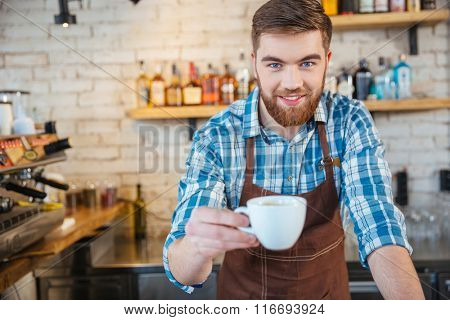 Handsome young barista with beard giving you white cup of coffee in coffee shop