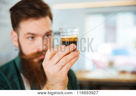 Barista holding glass with coffee in coffee shop. Focus on glass