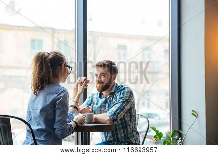 Happy young couple holding hands and drinking coffee in cafe